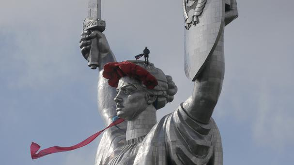 A man hangs a wreath of poppies on top of the 102-metre Motherland Monument in Kiev. (AP)