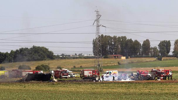 Emergency services work at the scene after a plane crash near Seville airport in Spain (AP)