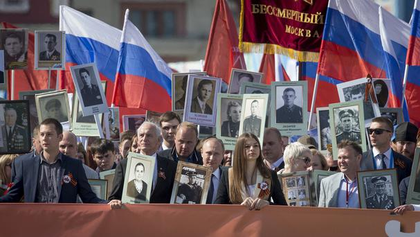 Russian president Vladimir Putin, centre, joined the vast crowd as the first marchers reached Red Square (AP)