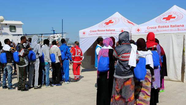 Migrants line up to enter a Red Cross tent after disembarking from the Migrant Offshore Aid Station vessel Phoenix in Sicily, southern Italy Credit: AP Photo/Francesco Malavolta