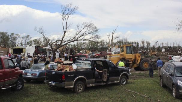People gather to help with clean-up efforts at a farm that was severely damaged by a tornado. (AP)