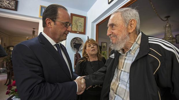 Cuba's former leader Fidel Castro, right, shakes hands with French President Francois Hollande in Havana (AP)