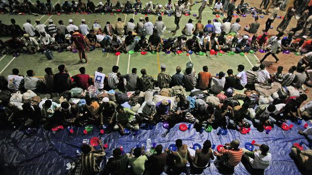 Migrants whose boats washed ashore on Sumatra island sit in lines for dinner at a sports stadium turned into temporary shelter. (AP)