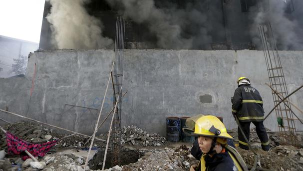 Firemen prepare to enter a still-smoldering Kentex rubber slipper factory in Valenzuela city, a northern suburb of Manila, Philippines. (AP)