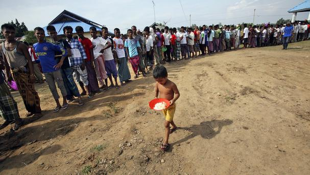 A Rohingya boy carries a plate in his hands as he walks past migrants queuing up for their meals during breakfast time at a temporary shelter in Lapang, Aceh province, Indonesia (AP)
