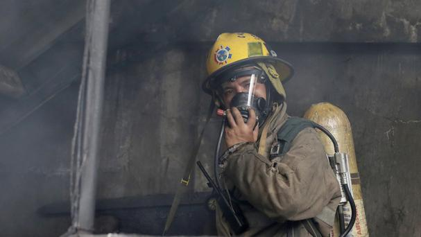 A fireman wearing an oxygen mask searches the Kentex rubber slipper factory in the Philippines (AP)