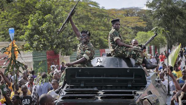 A Burundi soldier joins demonstrators celebrating an attempted military coup. (AP)