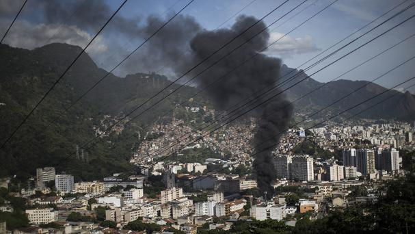 Smoke over Rio de Janeiro as protesters condemn the deaths of the two young men. (AP)