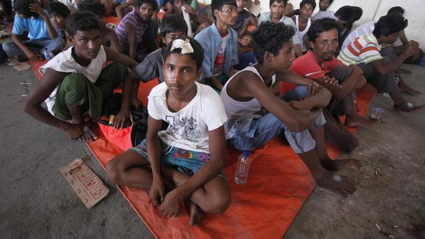 Newly arrived Rohingya migrants sit inside a temporary shelter at Kuala Langsa Port in Indonesia (AP)