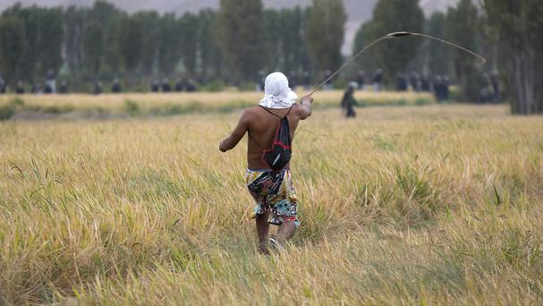 A farmer opposed to a mining project readies a slingshot to throw a stone at police in Cocachacra (AP)