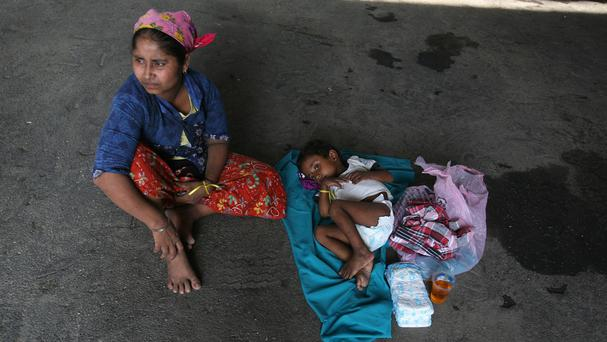 An ethnic Rohingya woman sits with her daughter under a tent at a temporary shelter in Langsa, Indonesia (AP)