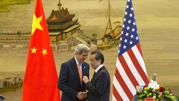John Kerry, left, and Wang Yi shake hands after a press conference in Beijing (AP)