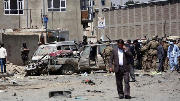 US and Afghan security forces inspect the site of a suicide attack near the international airport in Kabul (AP)
