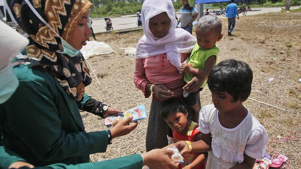 Students hand out snacks to ethnic Rohingya children at a temporary shelter in Langsa, Aceh province, Indonesia (AP)
