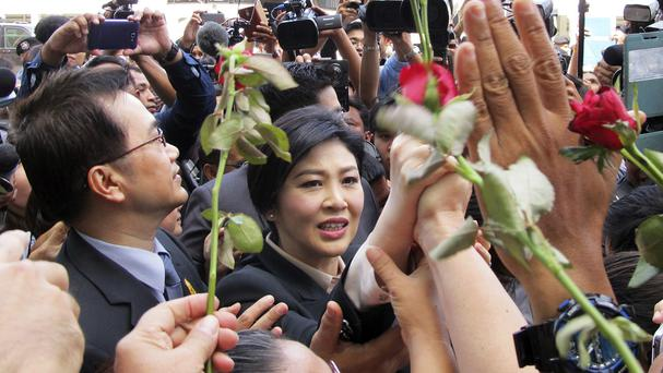Thailand's former prime minister, Yingluck Shinawatra, centre, walks through supporters as she leaves the Supreme Court in Bangkok (AP Photo/Thanyarat Doksone)