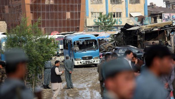 Afghan security forces inspect the site after a suicide car bombing attack in Kabul (AP)