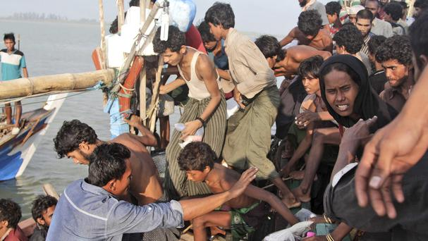 A fisherman, lower left, helps migrants on to his boat on the sea off East Aceh (AP)