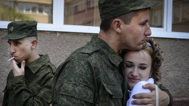 A draftee embraces his girlfriend in Simferopol, Crimea, where recruits are teaming up with Russian forces. (AP)