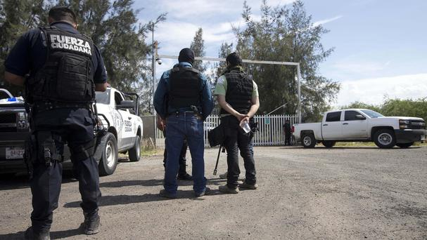 Police guard the entrance of Rancho del Sol, where more than 40 people were killed in a shoot-out with suspected drug traffickers (AP)