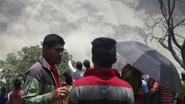 People gather at the site of the landslide north of Beni Bazaar (AP)