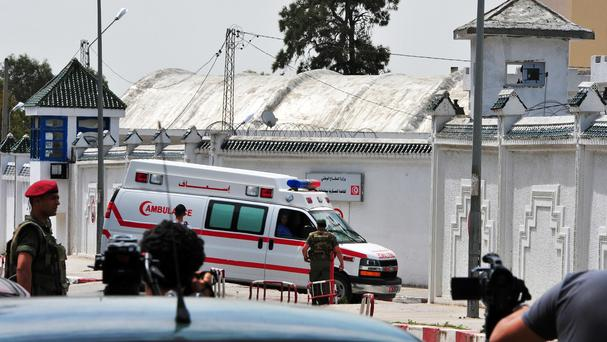 An ambulance arrives at the scene of a shooting at the Bouchoucha barrack in Tunis, Tunisia. (AP)
