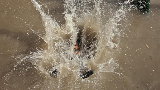 A boy jumps into the Ranbir water canal to cool off on a hot summer day in Jammu, India (AP)
