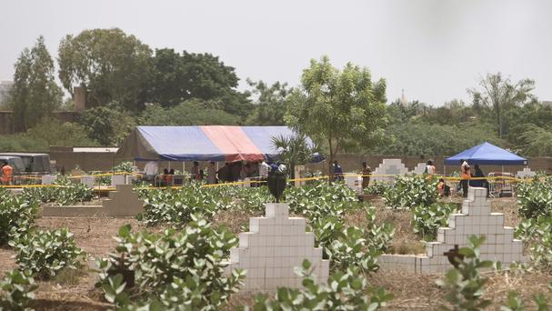 Graves are exhumed at Dagnoen cemetery on the outskirts of Ouagadougou, Burkina Faso (AP)