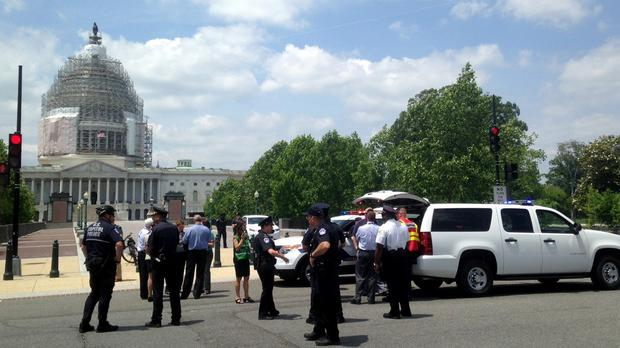 Capitol Hill police and visitors stand outside the building after the area was evacuated (AP)