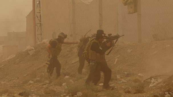 Security forces defend their headquarters against attacks by Islamic State extremists during a sandstorm in Ramadi, the capital of Anbar province (AP)