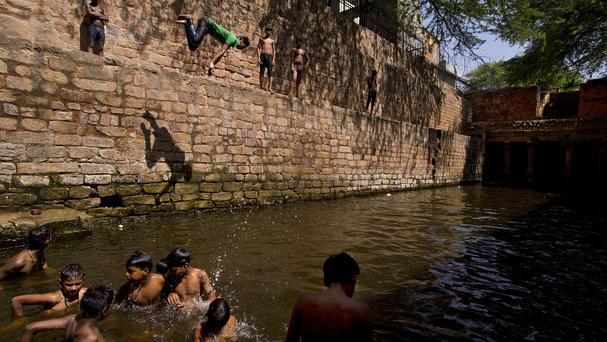 A young boy dives into a water tank on a hot summer day in New Delhi, India, (AP)