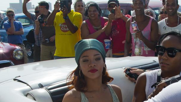 Fans take pictures of Rihanna, wearing a green head scarf and sitting in the backseat of an American classic car, in Havana (AP)