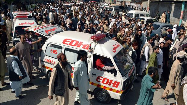 People escort ambulances carrying the bodies of passengers who were killed by gunmen when they hijacked two buses in Pakistan (AP)