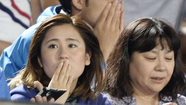 Japanese soccer fans react to a strong earthquake as they watch a J-League soccer match between the Shonan Bellmare and the Sanfrecce Hiroshima at BMW Stadium in Hiratsuka, southwest of Tokyo (AP)