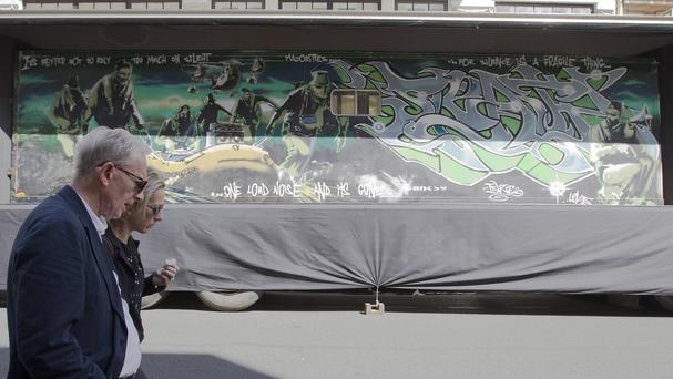 People walk past a trailer which street artist Banksy turned into a piece entitled