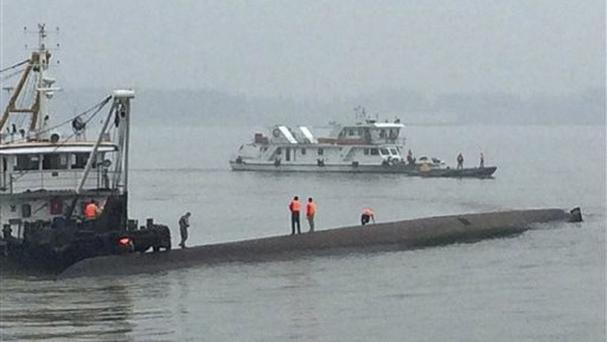 Rescue workers stand on the capsized ship on the Yangtze River in central China's Hubei province (Chinatopix/AP)