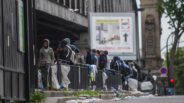 Migrants stand near a train station before being evacuated by police from a tent camp in Paris (AP)