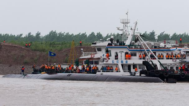 Rescue workers gather on the hull of the capsized cruise ship on the Yangtze River in central China's Hubei province (AP)
