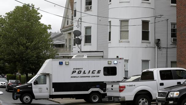 Police vehicles at a home in Everett, Massachusetts, which was being searched in connection with a man shot and killed earlier in the day in Boston (AP)