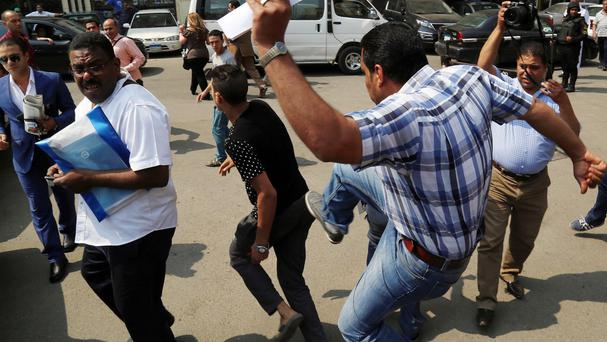 Supporters and opponents of ousted Egyptian president Hosni Mubarak, scuffle after a court session that ordered his retrial. (AP)