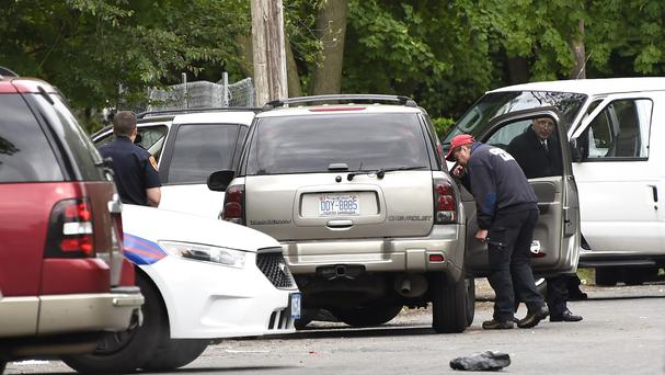 Police investigate the SUV car where three people were shot dead. (AP)