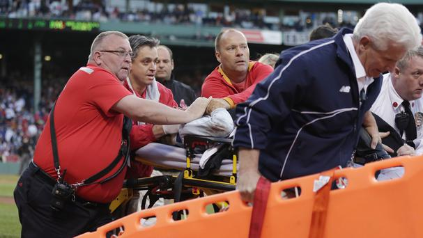 Boston Red Sox medical personnel tend to the woman who was hit by a wooden shard off a broken bat at Fenway Park, Boston (AP)
