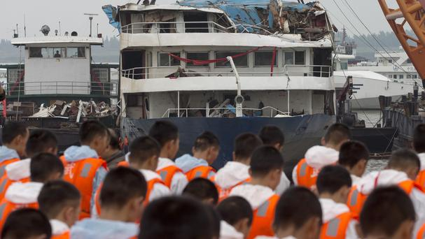 Rescuers bow during a memorial service near the raised capsized ship Eastern Star on the Yangtze River (AP)