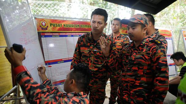 Members of the Malaysian rescue team plan as they wait for victims to be evacuated a day after an earthquake (AP)