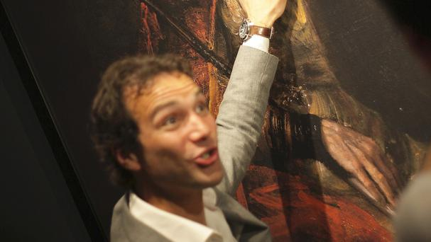 A Dutch television reporter strokes a 3D printed version of Rembrandt's Saul and David. (AP)