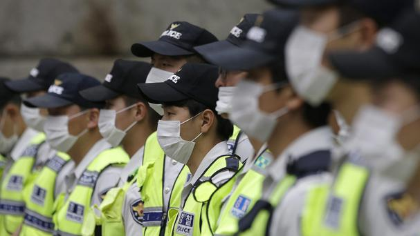 South Korean police officers wearing masks as a precaution against Mers stand guard in Seoul. (AP)