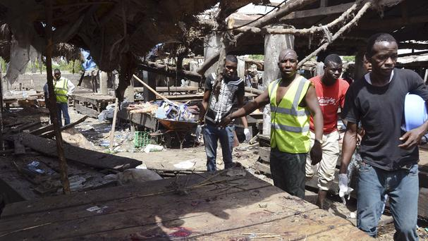 Rescue workers at the site of a Boko Haram bomb attack at a market in Maiduguri, Nigeria (AP)