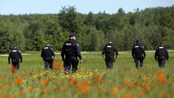 Law enforcement officers scour a field in the search for two escaped killers (AP)