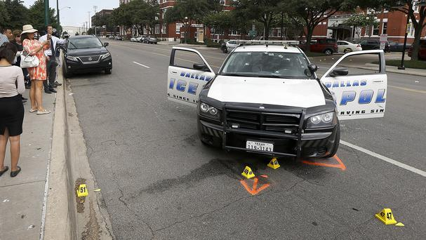 A police car with bullet holes in the windscreen after a gunman opened fire at Dallas Police headquarters (AP)