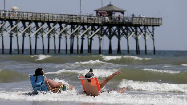 Holidaymakers venture back into the surf in Oak Island, North Carolina (AP)