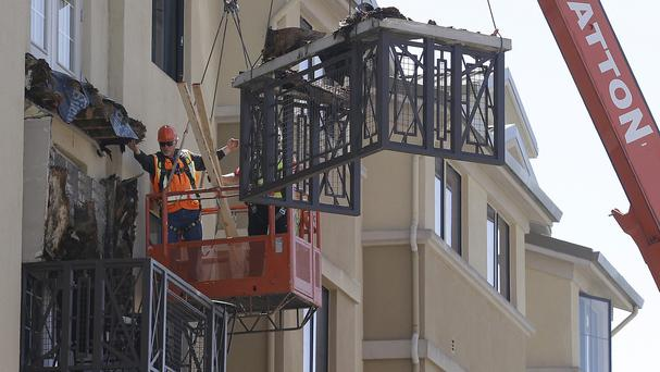 Workers remove part of a fourth floor balcony that fell onto the balcony below at the Library Gardens apartment complex in Berkeley (AP)